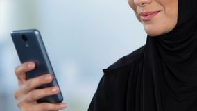 Smiling arab woman reading message on mobile phone, on-line chat, technology stock footage