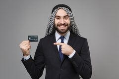 Smiling arabian muslim businessman in keffiyeh kafiya ring igal agal classic suit isolated on gray background