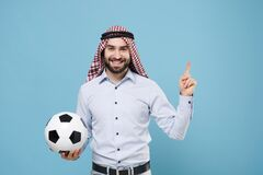Smiling arabian muslim man in keffiyeh kafiya ring igal agal casual clothes isolated on blue background. People