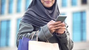 Smiling Arabic lady outdoors chatting on phone holding shopping bags, gadget. Stock photo royalty free stock photos