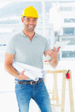 Smiling architect with blueprints and clipboard in office Royalty Free Stock Images