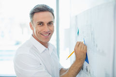 Smiling architect drawing on blueprint at whiteboard Royalty Free Stock Image