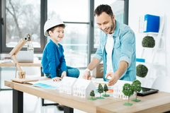 Smiling architect explaining basics of his work to his son. Clear explanation. Cheerful young architect explaining the basics of his work to his little son Royalty Free Stock Photos