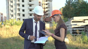 Smiling architect and foreman checking project on tablet outdoor. 4K stock video
