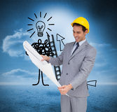 Smiling architect with hard hat looking at plans. Composite image of smiling architect with hard hat looking at plans Royalty Free Stock Image