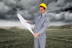Smiling architect with hard hat looking at plans Stock Photos