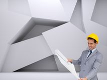 Smiling architect with hard hat looking at plans Royalty Free Stock Photos