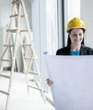 Smiling architect in a hardhat examining a blueprint in an office building Stock Photography