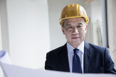 Smiling architect in a hardhat examining a blueprint in an office building Stock Photos