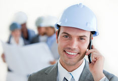Smiling architect with a hardhat on phone Royalty Free Stock Image