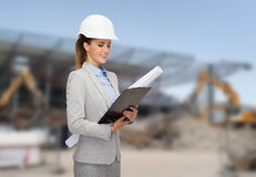 Smiling architect in helmet with blueprint Stock Photo