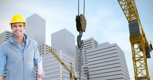 Smiling architect holding blueprints by crane against buildings. Digital composite of Smiling architect holding blueprints by crane against buildings Royalty Free Stock Image