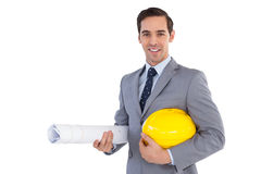 Smiling architect holding plans and hard hat Royalty Free Stock Images