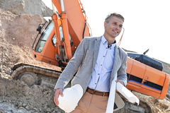 Smiling architect looking away while holding blueprints and hardhat at construction site Royalty Free Stock Photography