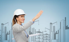 Smiling architect in white helmet with blueprints Stock Photography