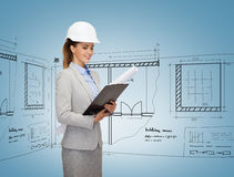 Smiling architect in white helmet with blueprints Stock Photo