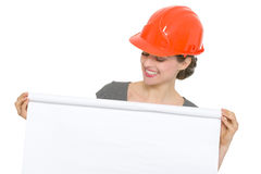 Smiling architect woman looking on blank flipchart Royalty Free Stock Photography