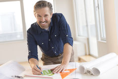 Smiling Architect Working On Blueprint At Desk Stock Images