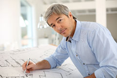 Smiling architect working on construction plan Stock Photography