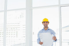 Smiling architect in yellow hard hat with blueprint in office. Portrait of a smiling young architect in yellow hard hat with blueprint in a bright office Stock Photo