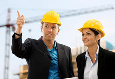 Smiling architects. Happy architects wearing protective helmet working and talking on contruction site Royalty Free Stock Images