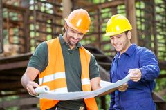 Smiling Architects Analyzing Blueprint At Site. Smiling male architects analyzing blueprint outside at construction site Royalty Free Stock Photo