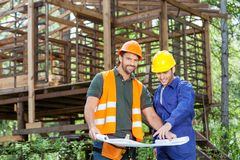 Smiling Architects With Blueprint At Construction stock photography
