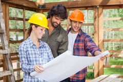 Smiling Architects Discussing Over Blueprint At. Smiling male and female architects discussing over blueprint in wooden cabin at site Stock Photos