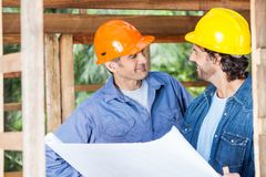 Smiling Architects Discussing Over Blueprint At Stock Photos