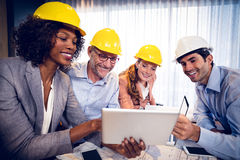 Smiling architects discussing over digital tablet in office Royalty Free Stock Photo