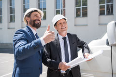 Smiling architects in hardhats holding blueprint and showing thumb up Stock Images