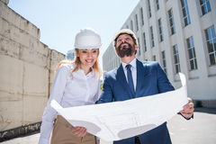 Smiling architects holding blueprint and working together. Two smiling architects holding blueprint and working together Royalty Free Stock Image