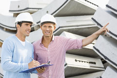 Smiling architects inspecting stock at site Stock Photos