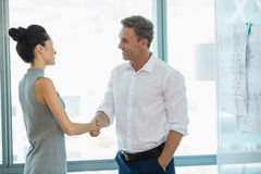 Smiling architects shaking hands with each other. In office Royalty Free Stock Photo