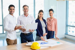 Smiling architects standing together in office. Portrait of smiling architects standing together in office Royalty Free Stock Images