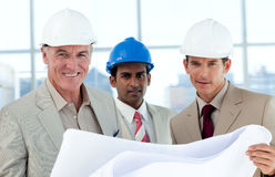 Smiling architects studying blueprints. In a building Stock Photos
