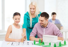 Smiling architects working in office. Startup, education, architecture and office concept - smiling architects with house model and blueprint working in office Stock Images