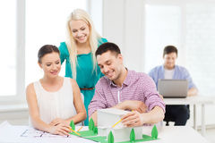 Smiling architects working in office. Startup, education, architecture and office concept - smiling architects with house model and blueprint working in office Stock Image