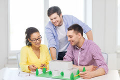 Smiling architects working in office. Startup, education, architecture and office concept - smiling architects with house model and blueprint working in office Royalty Free Stock Images