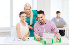 Smiling architects working in office. Startup, education, architecture and office concept - smiling architects with house model and blueprint working in office Stock Photography