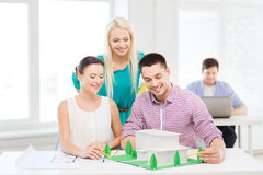 Smiling architects working in office. Startup, education, architecture and office concept - smiling architects with house model and blueprint working in office Royalty Free Stock Photography