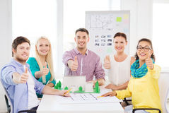 Smiling architects working in office. Startup, education, architecture and office concept - smiling architects with house model and blueprint showing thumbs up Stock Images