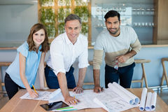 Smiling architects working over blueprint in conference room. Portrait of smiling architects working over blueprint in conference room at office Royalty Free Stock Photos