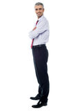 Smiling arms crossed senior businessman. Confident businessman with arms crossed Stock Photos