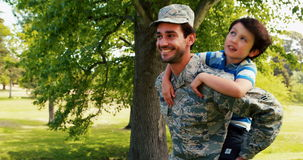 Smiling army soldier giving piggyback ride his son in park. On a sunny day stock footage
