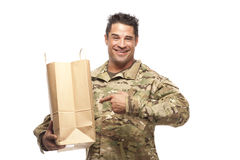Smiling Army Soldier with shopping bag. Happy Army soldier pointing at his shopping bag in front of a white background Stock Photo