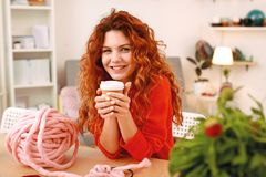 Smiling art student drinking take away coffee at the art class. Take away coffee. Smiling red-haired skillful art student drinking tasty take away coffee at the royalty free stock photography