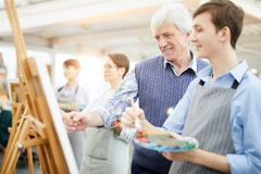 Smiling Art Teacher Helping Students. Waist up portrait of smiling art teacher helping student painting picture on easel during class, copy space royalty free stock photos