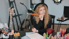 Artist with paintbrushes. Smiling artist holding paintbrushes, sitting at black desk full of pencils, having a break before creating another masterpiece stock video footage