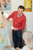 Smiling artist teaching people in painting studio. Stock Photos